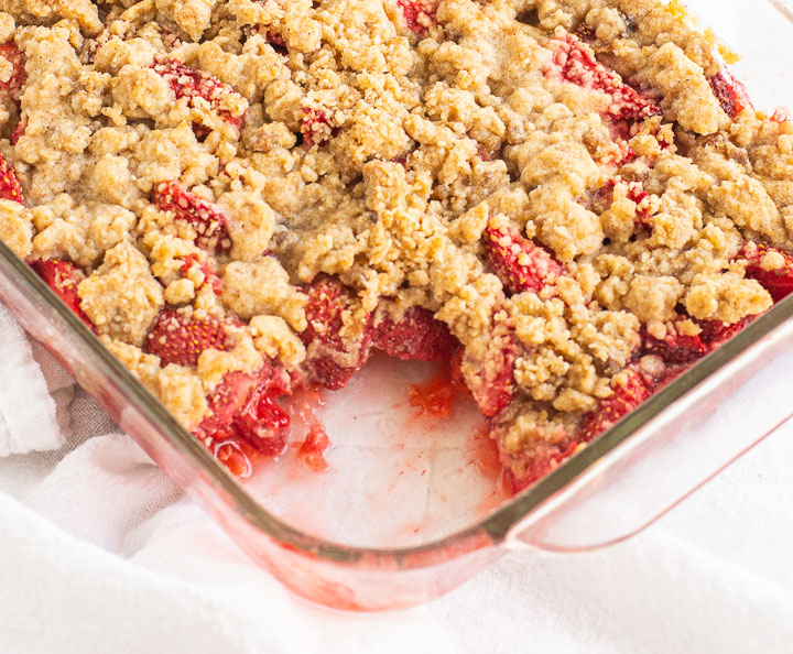 crumble in a baking pan with a scoop taken out of it