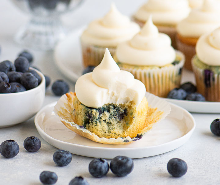 cupcake with a bite taken out of it on a plate with blueberries scattered in front and a plate with more cupcakes behind