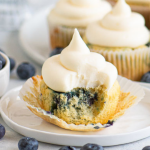 pinterest image of a blueberry cupcake with a bite taken out of it with text overlay