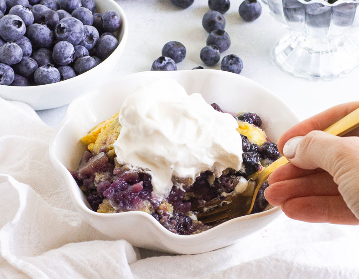 bowl of cobbler in front of a dish of blueberries with a hand holding a fork taking a bite out of the cobbler