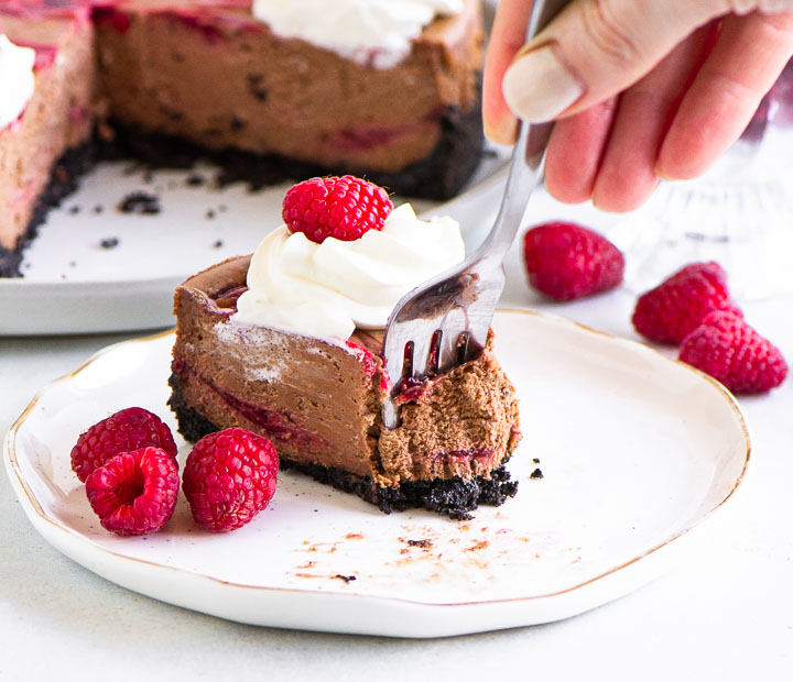 slice of raspberry chocolate cheesecake on a plate with hand holding a fork taking a bite out of the slice