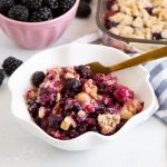 crumble in a bowl with a dish of blackberries behind it