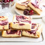 cheesecake bars on a wire rack in front of a plate with more bars and three cherries