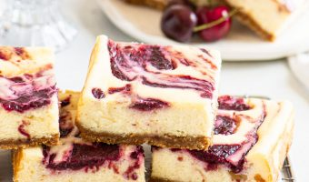 cheesecake bars stacked on a rack in front of a plate with more bars on top