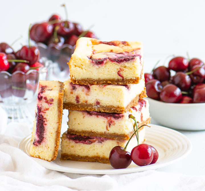 stack of cherry cheesecake bars on a plate in front of a bowl of fresh cherries