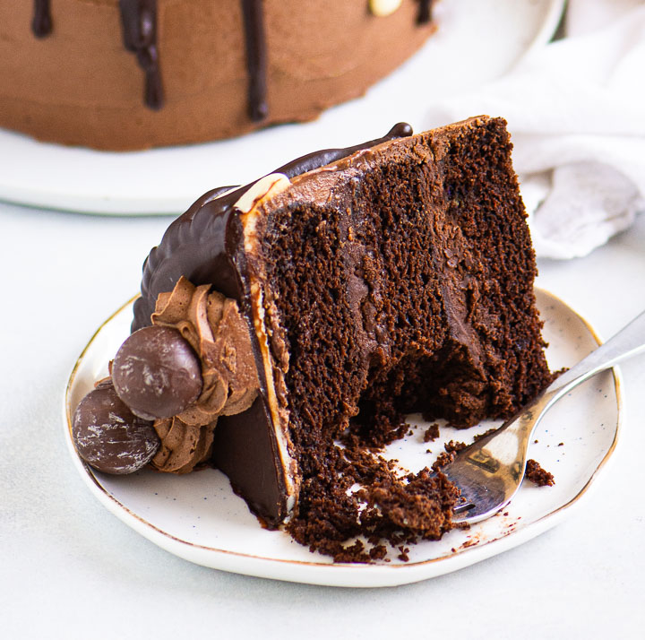 slice of chocolate cake on a plate with a fork taking a bite out of it