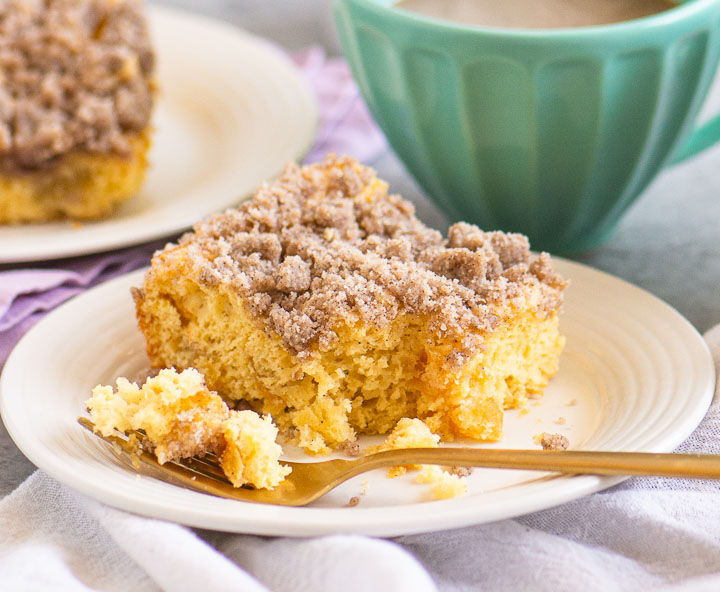 coffee cake on a plate with a mug of coffee and a second plate of cake behind it
