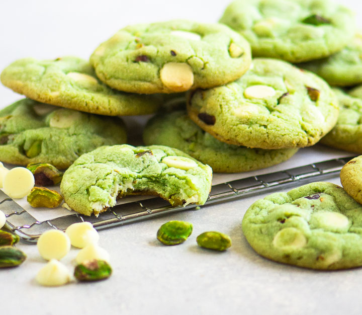 pistachio pudding cookies on a wire rack with pistachios and white chocolate chips in the foreground
