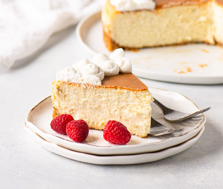 slice of cheesecake on two plates with raspberries in front of the rest of the cheesecake on a serving plate