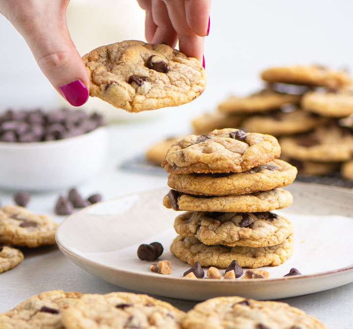 hand lifting a cookie off of a stack of cookies on a plate