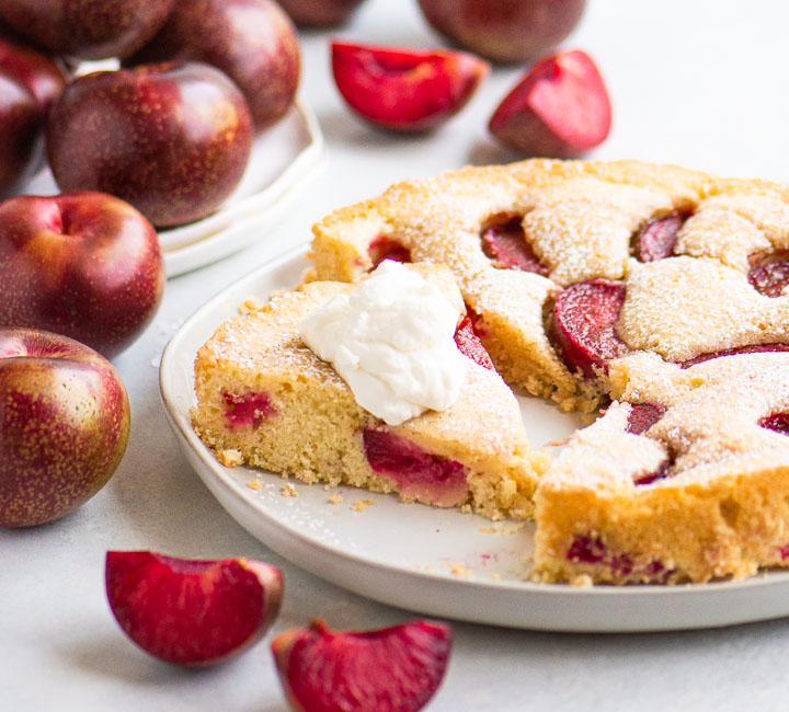 sliced plum cake with whipped cream on a cake plate surrounded by plums