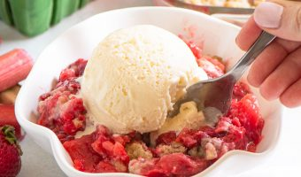 hand reaching into a bowl of crumble topped with ice cream