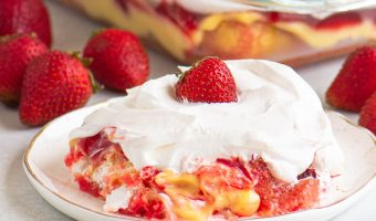 scoop of cake on a plate in front of a baking dish surrounded by strawberries