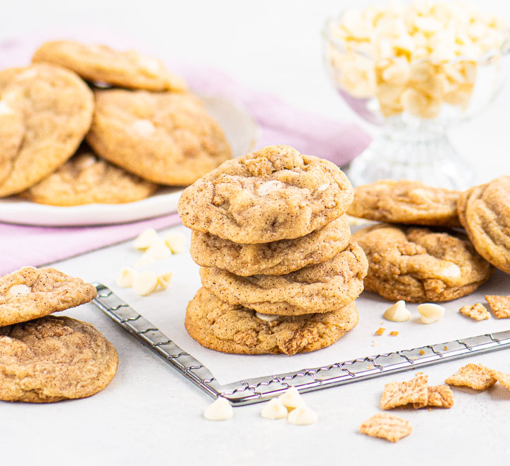 stack of cookies on a wire rack in front of a plate holding more cookies