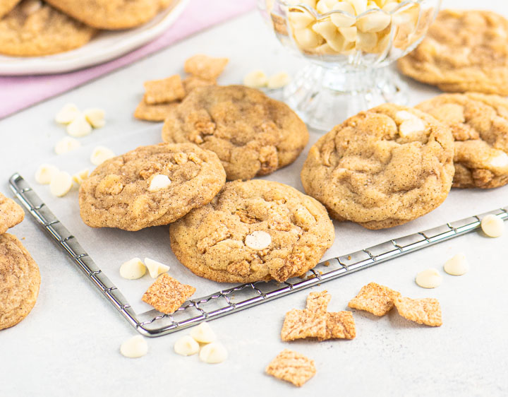 Cinnamon Toast Crunch cookies on a wire rack in front of a dish of white chocolate chips